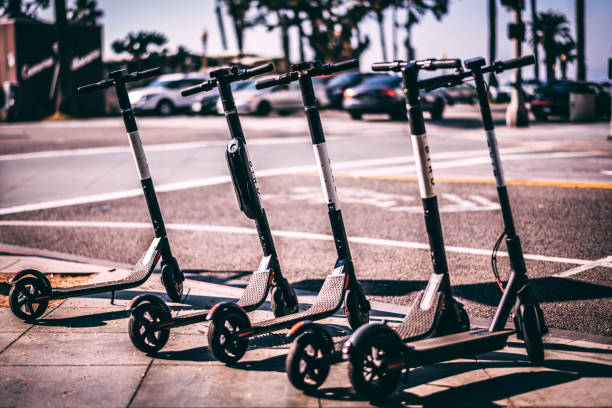 bird electric scooters parked in a row on a sidewalk - electric push scooter stock photos and pictures