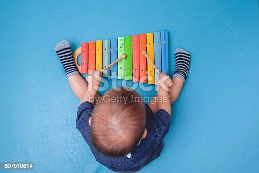 istock Bird eye view of Cute little Asian 18 months / 1 year old baby boy child hold sticks & plays a musical instrument colorful wooden toy xylophone 807510614