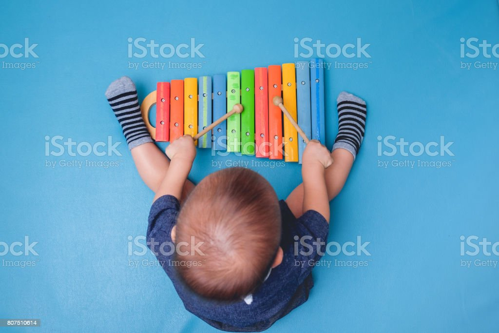 Bird eye view of Cute little Asian 18 months / 1 year old baby boy child hold sticks & plays a musical instrument colorful wooden toy xylophone stock photo