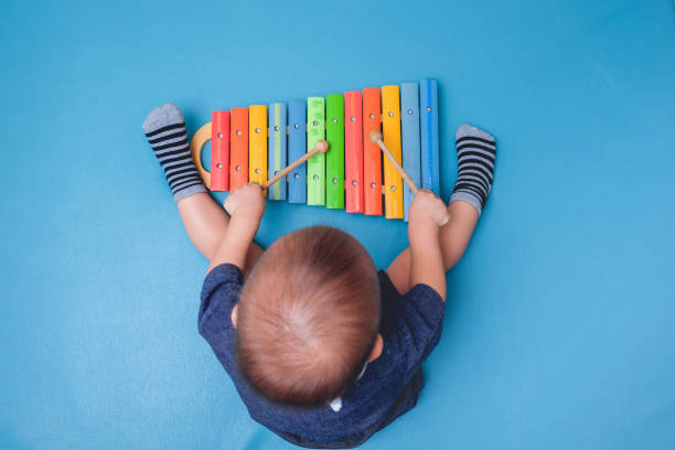 bird eye view of cute little asian 18 months / 1 year old baby boy child hold sticks & plays a musical instrument colorful wooden toy xylophone - music stock photos and pictures