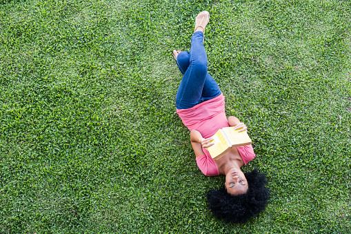 Portrait of lady lying on the grass reading