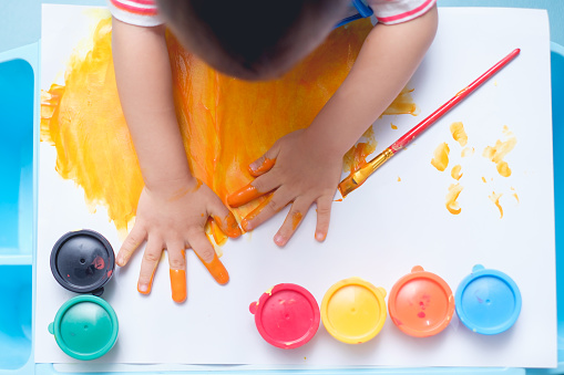 1042756824 istock photo Bird eye view / Top view of little Asian 18 months / 1 year old toddler baby boy child finger painting with hands and watercolors 938434710