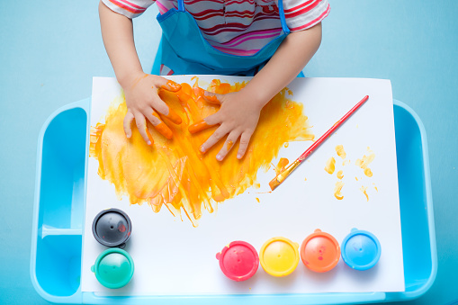 1042756824 istock photo Bird eye view / Top view of little Asian 18 months / 1 year old toddler baby boy child finger painting with hands and watercolors 938434848