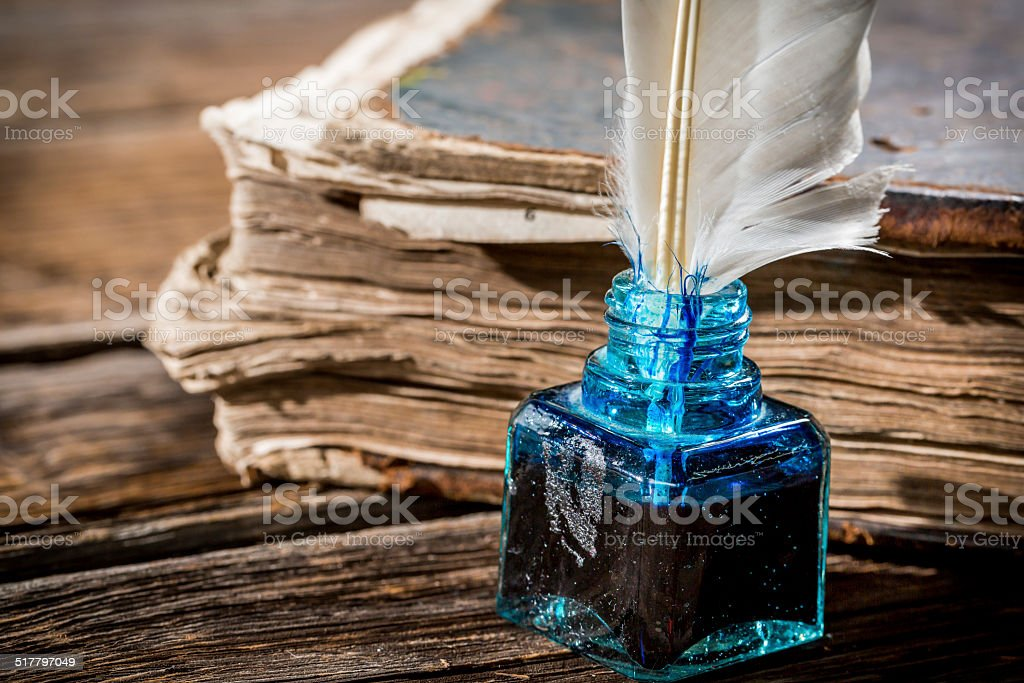 Bird feather in the inkwell and old book stock photo