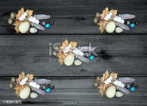 istock Bird feathers, stones, eggs, oak leaves, acorns, maple leaves on wooden background on top view. 3D render 1182841971