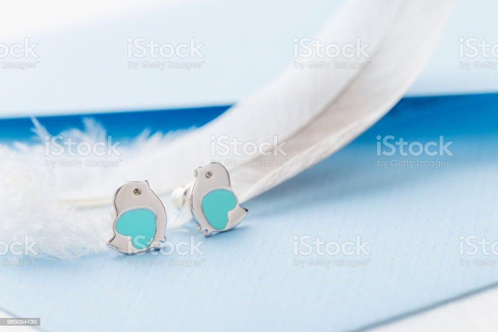 Bird shape with heart earring studs on blue background with feather zbiór zdjęć royalty-free