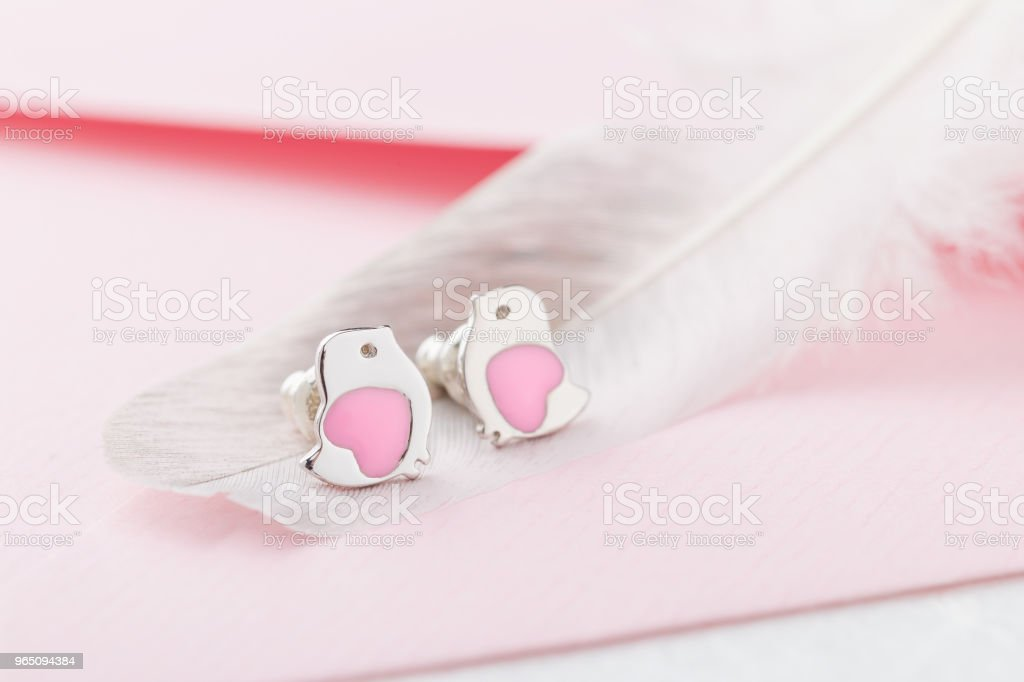 Bird shape with heart earring studs on pink background with feather zbiór zdjęć royalty-free