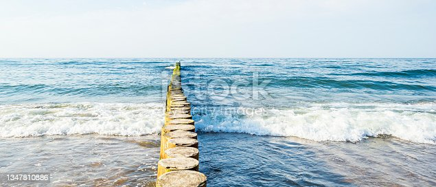 istock A bird sits in the distance on a wooden breakwater in a rough sea, seascape with a sea horizon 1347810886