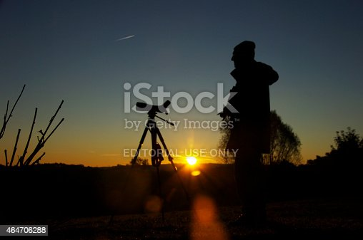 Brunssum, the Netherlands- October 15, 2011: Daybreak scene where a man is bird watching during an impressive sunrise early in the morning. He is waiting for the birds in this beautiful heathland area.