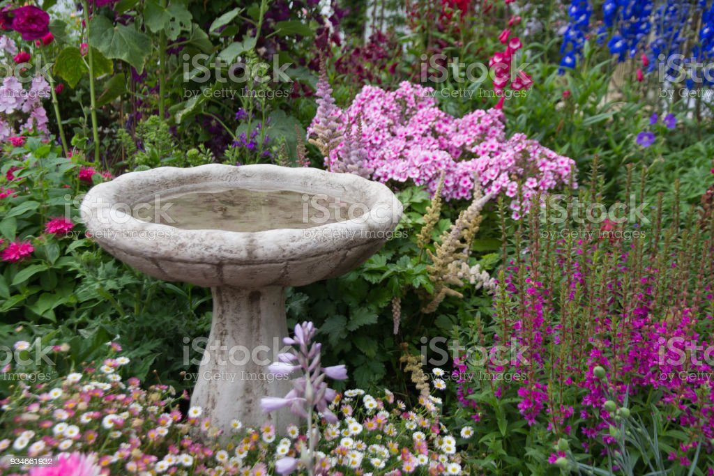 Birdbath surrounded by flowers stock photo