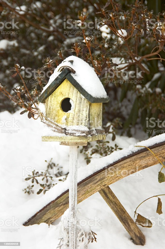 Birdhouse in Snow, Rustic and Weathered Yard Decoration royalty-free stock photo