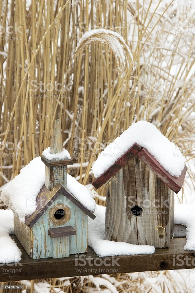 Birdhouses in Snow, Rustic and Weathered Yard Decoration royalty-free stock photo