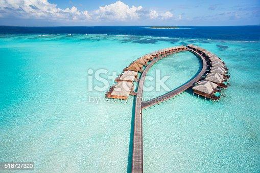 aerial view of luxury overwater villas in tropical lagoon of indian ocean