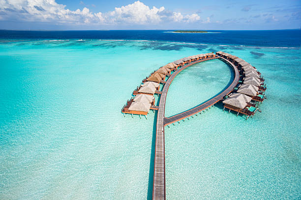 bird's eye view luxury overwater villas aerial view of luxury overwater villas in tropical lagoon of indian ocean bungalow stock pictures, royalty-free photos & images