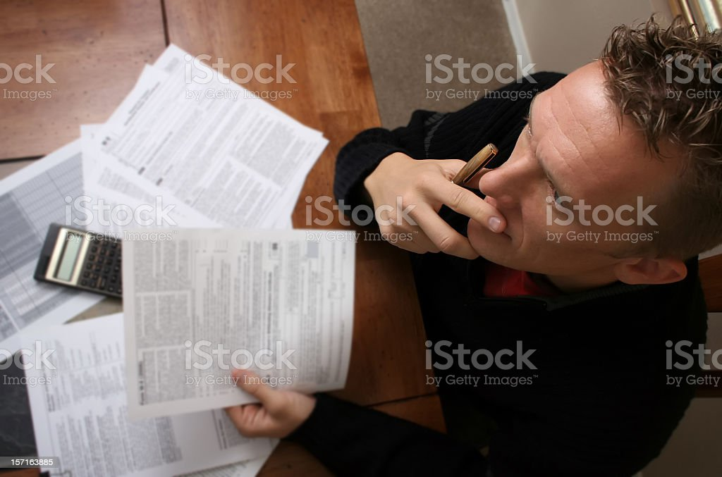 A birds eye view of a man doing his taxes Young man contemplates his tax statements. 1040 Tax Form Stock Photo
