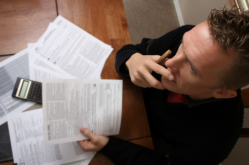 A Birds Eye View Of A Man Doing His Taxes Stock Photo - Download Image Now