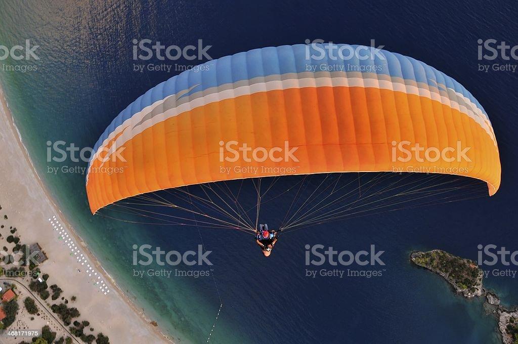 Birds eye view of a person paragliding over the ocean stock photo
