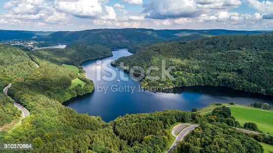 Bird's eye view over beautiful landscape with a lake and green forest from above taken by a drone