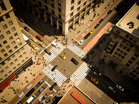 Bird's eye view of Manhattan, looking down at people and yellow taxi cabs going down 5th Avenue.  Toned, Instagram photography with slight vignette.