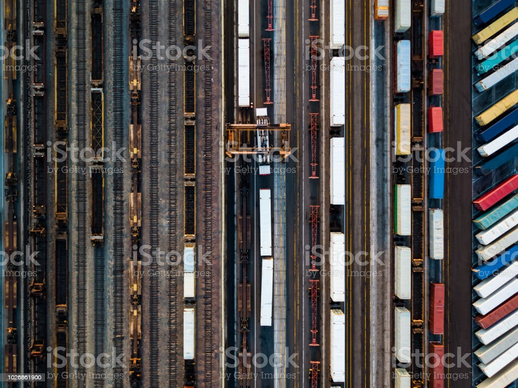 Birds Eye View of Shipping Containers Waiting Beside Freight Train stock photo
