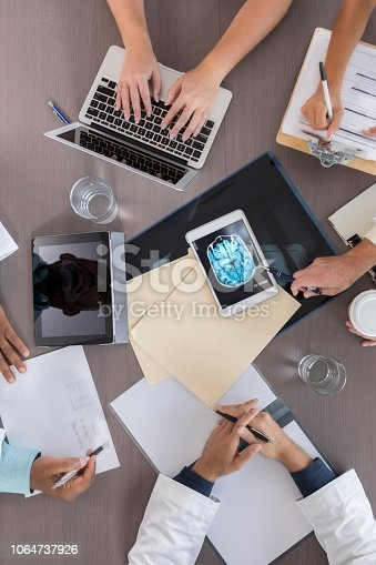 In this bird's eye view, a table is full of files, papers, water, a laptop computer, a clipboard, and digital tablets, one containing a brain x-ray image.  Only human hands can be seen as a group of doctors sit around the table during a meeting.