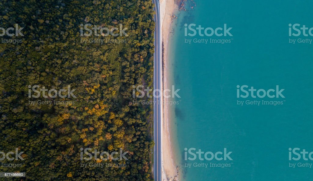 Birds eye view of winding road between a mountain and the ocean stock photo