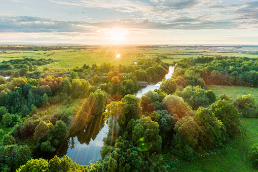 Landscape view from above. The countryside with a meadows, a groves and a winding river next to a town. Shooting at sunset in warm summer day