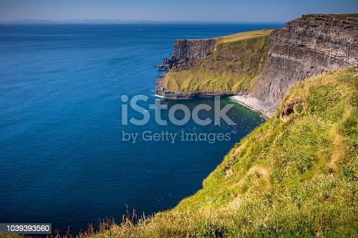 Looking north over the Cliffs of Moher, which are 200m high cliffs located at the southwestern edge of the Burren region in County Clare, Ireland. Birds are flying over the ocean below towards the cliffs.