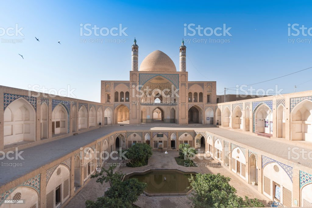 Birds flying over the sky above Agha Bozorgi school and mosque in Kashan, Iran. stock photo