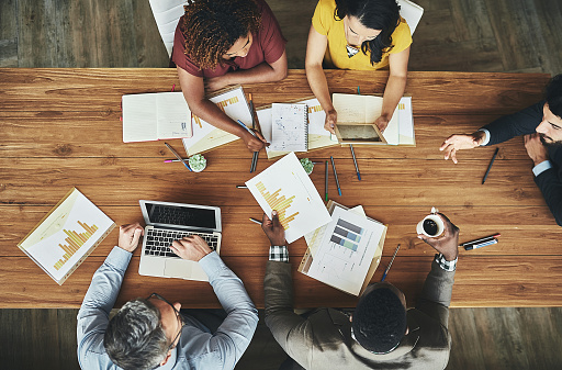 High angle shot of a team of businesspeople meeting around the boardroom table in the office