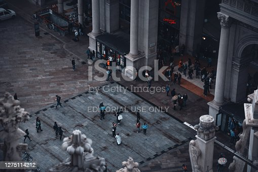 Milan, Italy - October 19, 2016: A bird's-eye view of a crowded street in the center of Milan with many tourists and locals taken from the roof of the Milan Cathedral on a rainy autumn day.