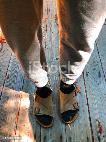 Birkenstock Sandals and sweatpants: Man standing on wood deck with socks and sandals.