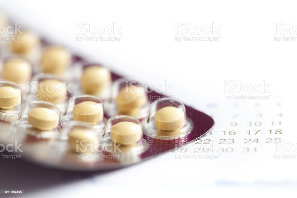 Birth control pills macro with calendar stock photo
