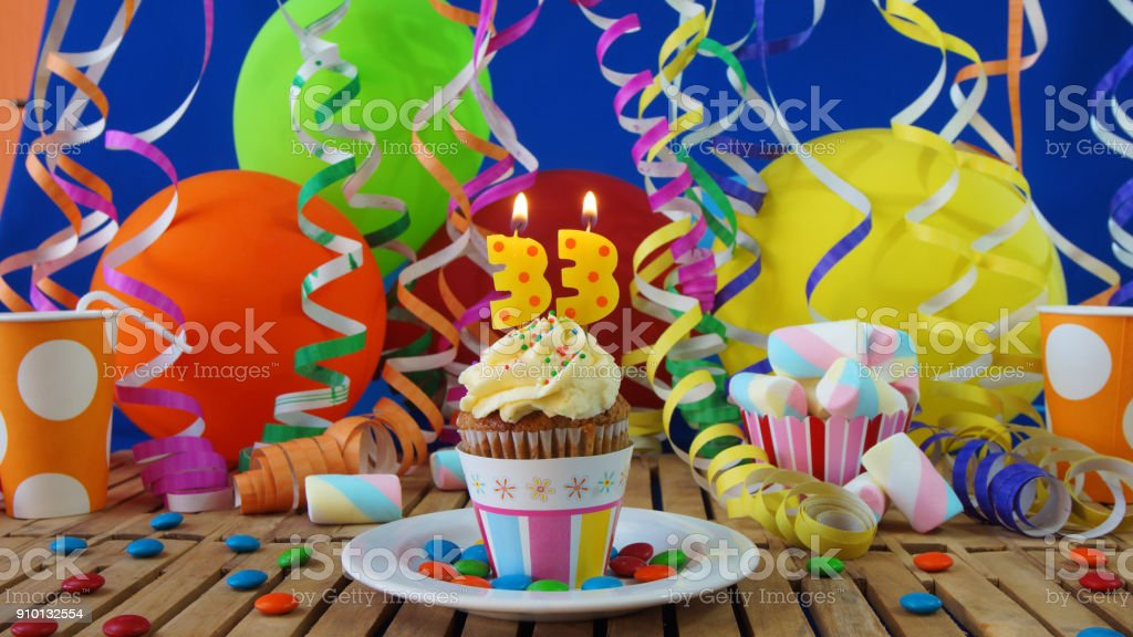 Birthday 33 cupcake with candles burning on rustic wooden table with background of colorful balloons, plastic cups and candies with blue wall in the background stock photo