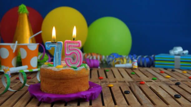 Birthday 75 Cake With Candles On Rustic Wooden Table Background Of Colorful Balloons Gifts Plastic Cups And Candies Blue Wall In The