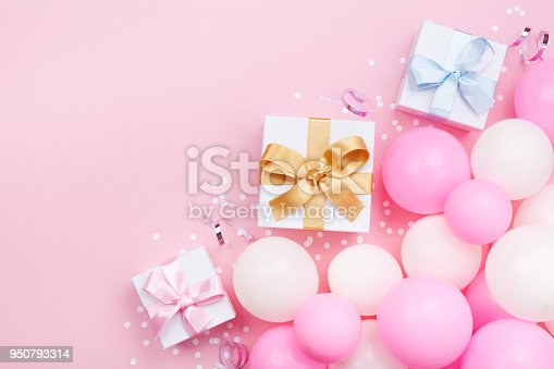 950793576 istock photo Birthday background with gift or present box, balloons and confetti on pink pastel table top view. 950793314