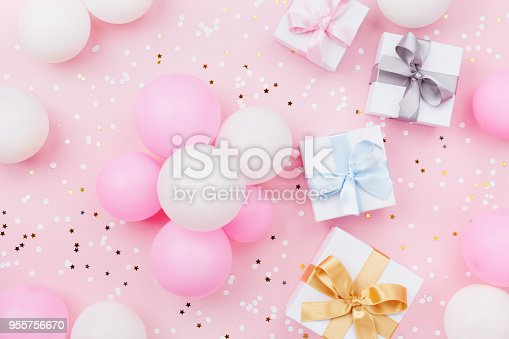 950793576 istock photo Birthday background with gift or present box, balloons and confetti on pink pastel table top view. Flat lay. 955756670