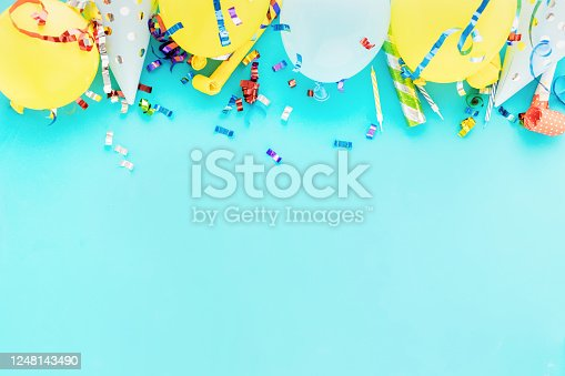 Birthday balloon background with colorful party streamers, confetti and birthday party hats on blue bacground top view