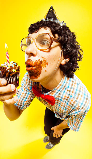 birthday boy disaster - nerd boy eating stock photos and pictures