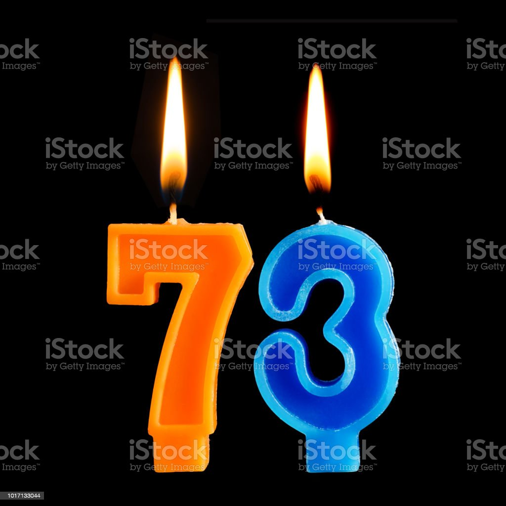 Birthday burning candles in the form of 73 seventy three for cake isolated on black background. stock photo