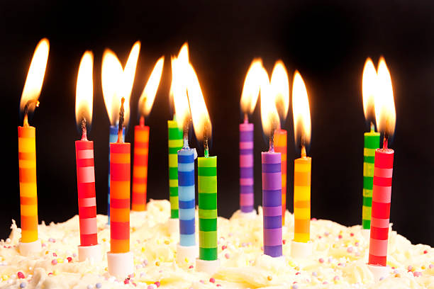 birthday cake and candles on black background stock photo