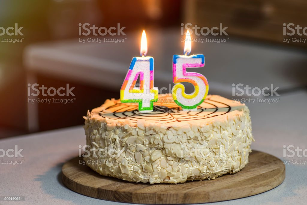 Birthday cake. Candles burn in the form of numbers 45. stock photo