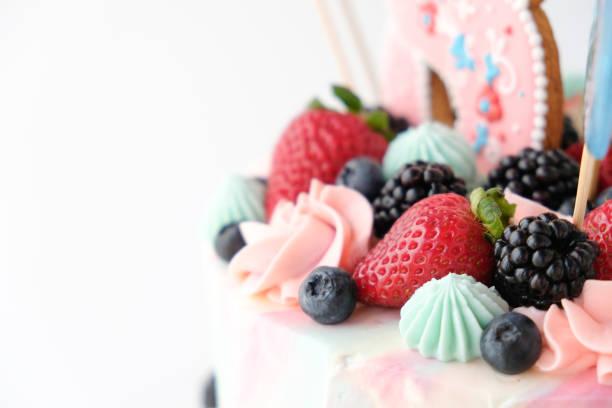 geburtstagstorte, dekoriert mit bunten süßigkeiten und beeren auf weißem hintergrund. - prinzessinnen torte stock-fotos und bilder
