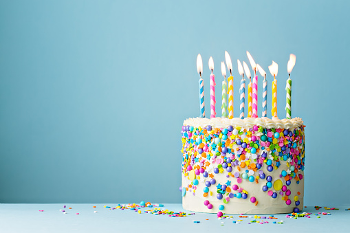 istock Birthday cake decorated with colorful sprinkles and ten candles 1136810581