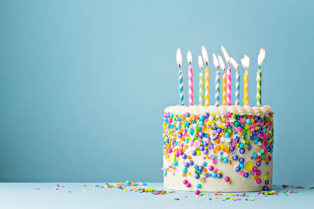 Birthday cake decorated with colorful sprinkles and ten candles Colorful birthday cake with sprinkles and ten candles on a blue background with copyspace cake stock pictures, royalty-free photos & images