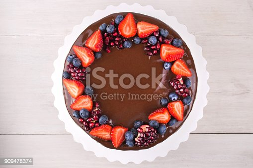 istock Birthday cake in chocolate with strawberries, blueberries and garnet on white wooden table. 909478374