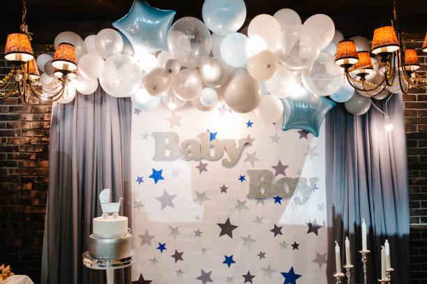 geburtstagstorte auf einem hintergrund blau, weiß und silber ballons, ziegelwand. baby-dusche-party, dekor. kuchen mit figurenwagen für einen jungen. kopieren sie den speicherplatz. feiertaufe konzept. - sterntaufe stock-fotos und bilder