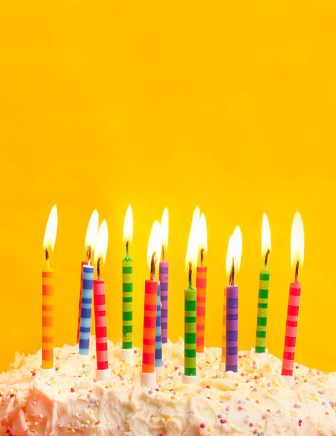 birthday cake on yellow background stock photo