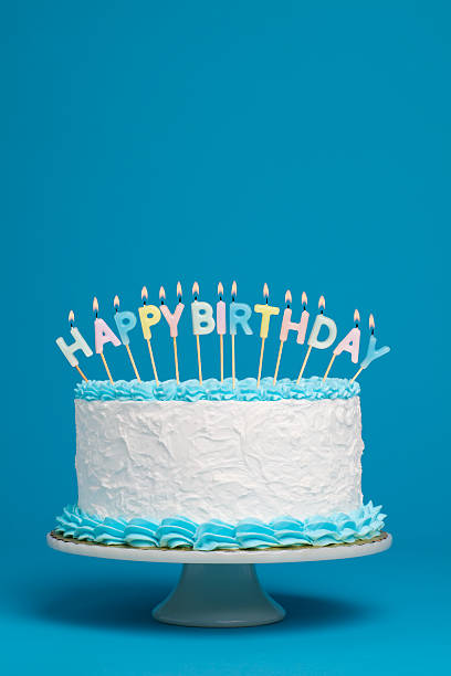 Birthday Cake A birthday cake with lit candles against a blue background.More cakes: birthday cake stock pictures, royalty-free photos & images