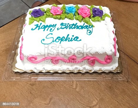 Birthday cake with handwritten Happy Birthday Sophia,  with vanilla frosting and flower frosting decorations on wood table